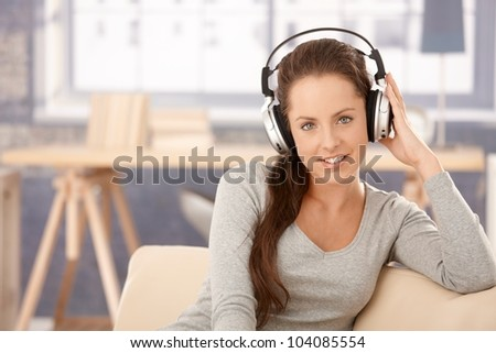 Attractive girl listening to music at home, sitting on sofa, using headphones. - stock photo
