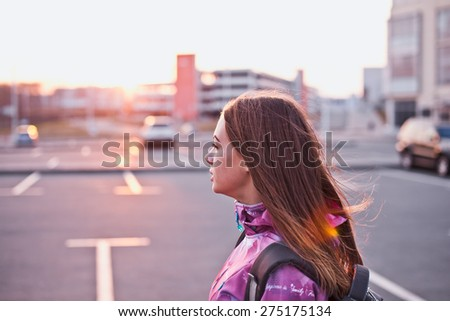 Attractive girl looking aside on a parking lot at a sunset. Traveling, backpacking, life and freedom concept. Profile view. Copy space - stock photo