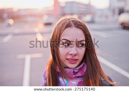Attractive girl looking aside on a parking lot at a sunset. Traveling, life and freedom concept - stock photo