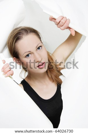 attractive girl looking out from hole in paper