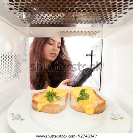 Attractive girl looks in a microwave and speak phone - stock photo