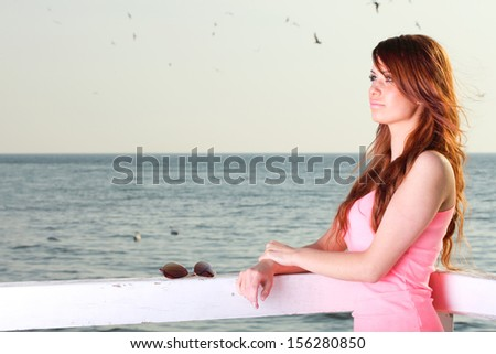 Attractive girl on pier Young woman on background of sea - stock photo