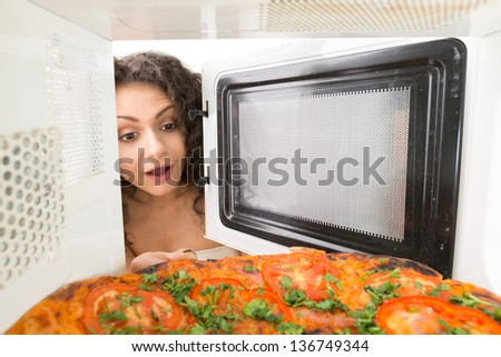 Attractive girl open  a microwave - stock photo