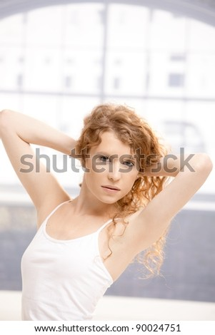 Attractive girl posing in dance studio holding up her hair.? - stock photo
