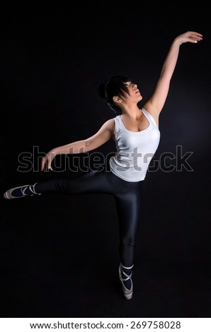 Attractive girl practicing ballet against a black background - stock photo