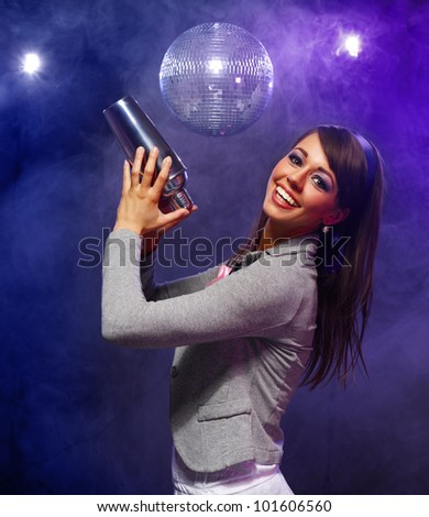 Attractive girl preparing a coctail in shaker - stock photo