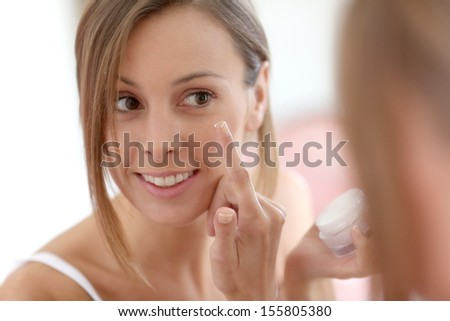 Attractive girl putting anti-aging cream on her face - stock photo