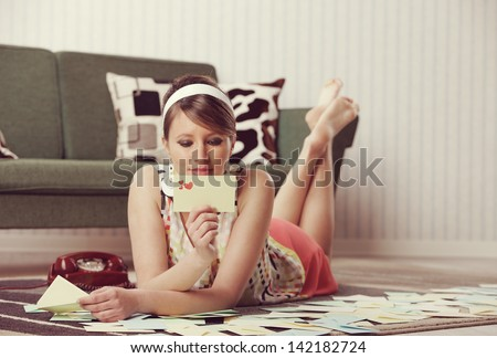 Attractive girl reading a Valentine card or loveletter