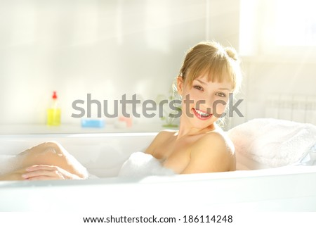 Attractive girl relaxing in bath on light background - stock photo