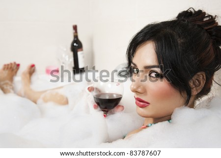 attractive girl relaxing in Jacuzzi and drinking red wine - stock photo
