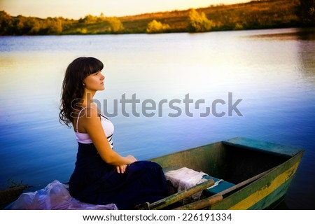 Attractive girl sailing in the boat on the river. Summer day, nature landscape.