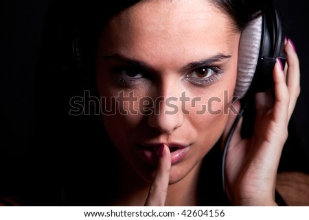 Attractive girl showing shh and listening music on her headphones