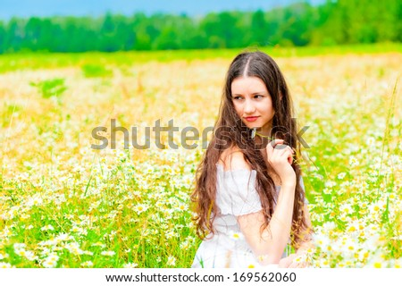 Attractive girl sitting in a field of daisies and looking away - stock photo