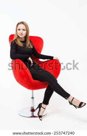 Attractive girl sitting on a red swivel chair - stock photo