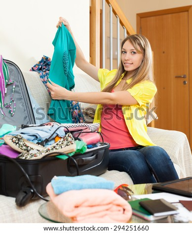 Attractive girl sitting on sofa and packing clothes in suitcase