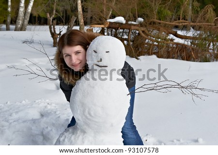 attractive girl standing beside a snowman - stock photo
