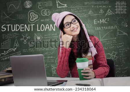 Attractive girl studying in the classroom and dreaming about student loan while wearing winter wear - stock photo
