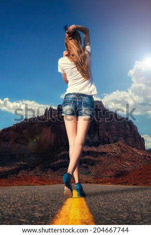 attractive girl walking along the road in the desert under the scorching sun - stock photo