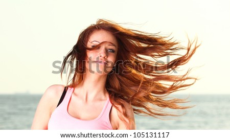 Attractive girl wind in hair Young woman on background of sea sky