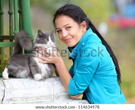 attractive girl with a cat in hands close-up - stock photo
