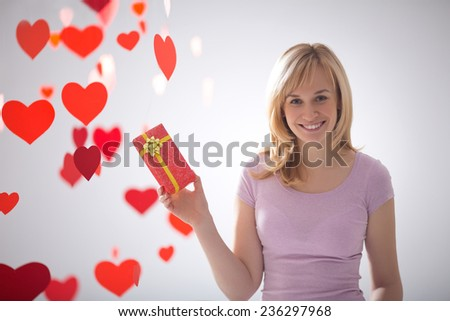 Attractive girl with a gift and hearts - stock photo