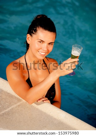 Attractive girl with a glass of champagne in the pool