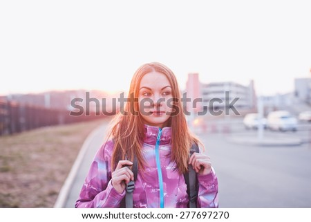 Attractive girl with backpack looking aside on a parking lot at a sunset. Urban scenery. Traveling, life and freedom concept - stock photo