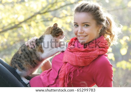 attractive girl with cat on natural background - stock photo