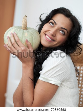 Attractive girl with dark hair sitting in a wicker chair, holding a green pumpkin and smiling