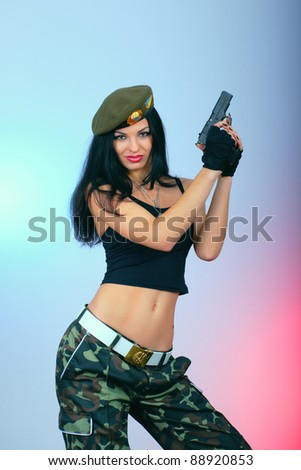 attractive girl with hand gun. military style wear