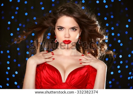 Attractive girl with makeup. Red lips. Jewelry Earring. Manicured nails. Expressive eyes stare. Elegant lady over studio blue lights on dark background. Luxury style. - stock photo