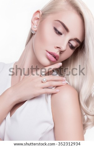 Attractive girl with perfect skin.A woman and a gift.Beautiful young woman close-up in the photo, her eyes looking to the bottom, on the face of the fresh make-up, white locks of hair beautifully laid - stock photo