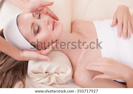 Attractive girl with perfect skin.Haired woman close up while lying on the massage table, her face massaged his hands beautician, a smile on his face.Woman and facial massage.Woman and spa.