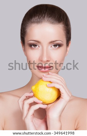 Attractive girl with perfect skin.Young woman advertises healthy food,fruit diet for each day,and the use of vitamins,healthy food for every day,woman and a lemon.Woman with perfect makeup on the face