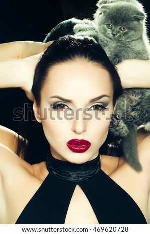 Attractive girl with red lipstick and the grey kitten behind