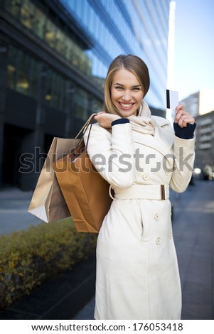 Attractive girl with shopping bags and credit card - stock photo