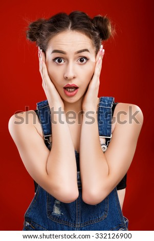 Attractive girl, with top knot hairdo, wearing on denim jumpsuit, posing like she is frightened, on the red background in studio, waist up - stock photo