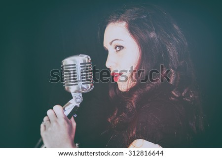 Attractive Girl with Vintage Microphone. Attractive female singing into a vintage microphone. Set in dark room with spot lighting and edited with vintage effects. - stock photo