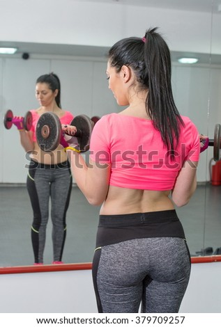 Attractive girl working out biceps in the gym