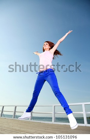 Attractive girl Young woman jumping in the sky