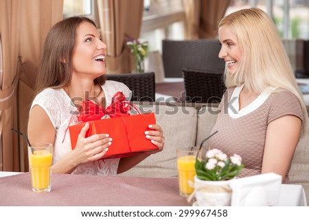Attractive girls are talking and sitting at the table in cafeteria. The brunette girl is receiving a gift from her friend. She is smiling with happiness and surprise. Her friend is laughing - stock photo
