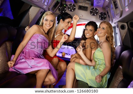 Attractive girls in evening dress having party in limo, smiling. - stock photo