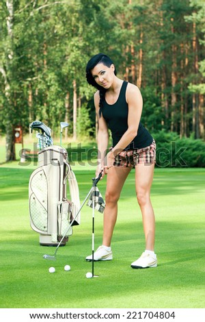 Attractive golfer girl on golf course - stock photo