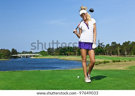 Attractive golfer girl on golf course with driver