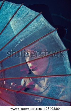 Attractive gothic lady in top hat looking through Chinese umbrella, artistic shot - stock photo