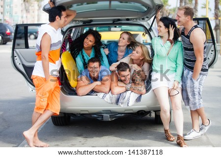 Attractive Group of young People gathered around an SUV at the Beach having fun Laughing and talking - stock photo