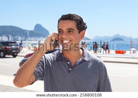 Attractive guy at Rio de Janeiro speaking at phone - stock photo