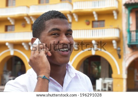 Attractive guy calling by phone in a colonial town - stock photo