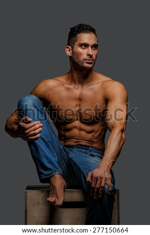 Attractive guy in blue jeans with naked torso sitting on a podium. GIsolated on grey background - stock photo