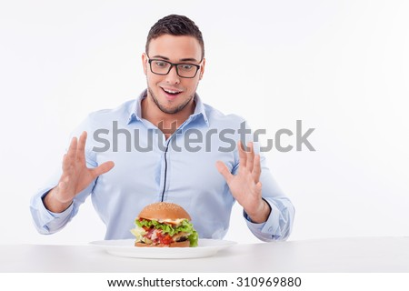 Attractive guy is looking at the hamburger with temptation. He is ready to eat it. The guy is sitting at the table and happily smiling. Isolated on background and copy space in right side - stock photo